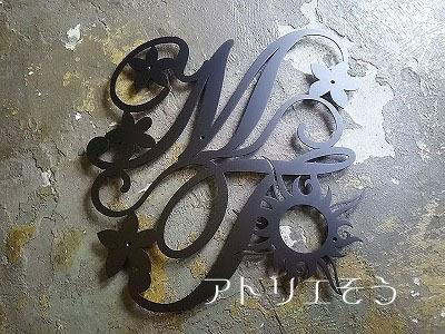 アトリエそうオリジナルデザインのロートアイアン風アルミ製妻飾り。イニシャルMとTにジャスミンの花と太陽を加えたとても素敵なアルミ製妻飾りの写真