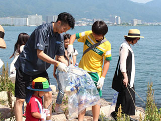 滋賀レイクスターズの選手と一緒に琵琶湖岸のゴミを拾う参加者