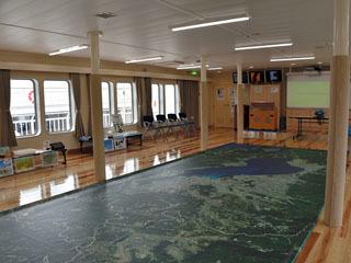 琵琶湖の空撮写真シートを展開した新うみのこの船内