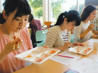 養殖ビワマスを試食する学生達