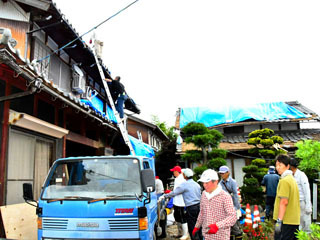 竜巻で被害を受けた民家を片付ける住民ら