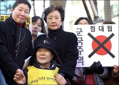 平成15年(2003年)2月12日、民主党(現:民進党)議員だった岡崎トミ子は、国民の血税で韓国に行って反日デモに参加し、ソウルの日本大使館に向かって朝鮮人売春婦への謝罪と賠償を請求した。