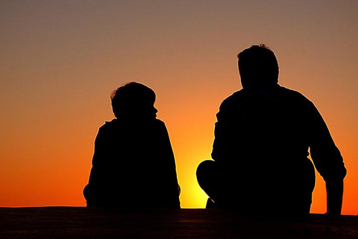 夕焼けを見る父と息子