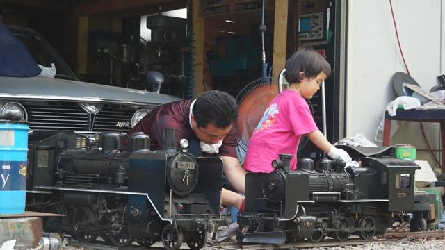 子供 小さな蒸気機関車を磨く